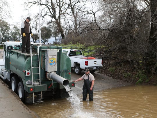 John Silva, Coleman National Fish Hatchery work leader, left, and maintenance manager Joe Livesay release steelhead trout into the Sacramento River near Red Bluff on Wednesday.
