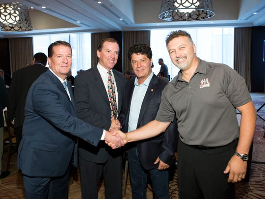 From left, FCA Canada lead negotiator James Dyckman and FCA US head of employee relations Glenn Shagena shake hands with Unifor President Jerry Dias and Unifor lead negotiator with FCA Dino Chiodo.
