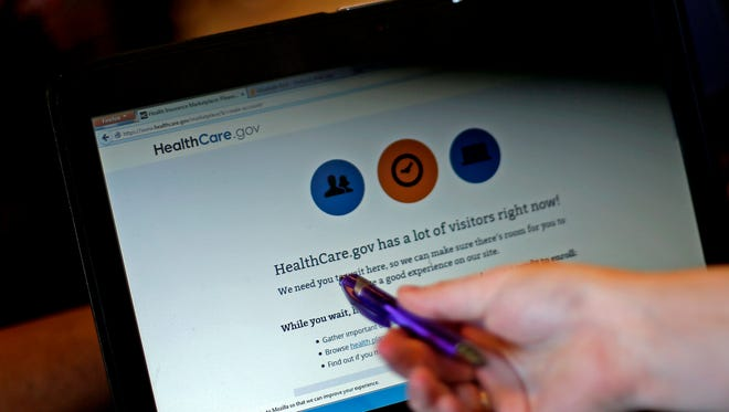 Elizabeth Rich points to a Web page for the Affordable Care Act as she helps people sign up for insurance at Swope Health Services on  March 31 in Kansas City, Mo.