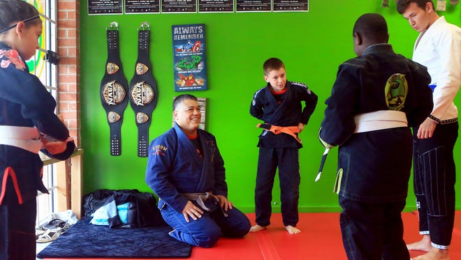 John Barrera (center) talks to students from the Strong Arm Mixed Martial Arts before the training on Thursday, April 13, 2017, in Corpus Christi. Barrera placed first in the regular division and open division of the Pan Jiu-Jitsu International Brazilian Jiu-Jitsu Federation Championship in March.