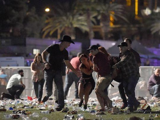 People carry a person at the Route 91 Harvest country music festival in Las Vegas Sunday night.