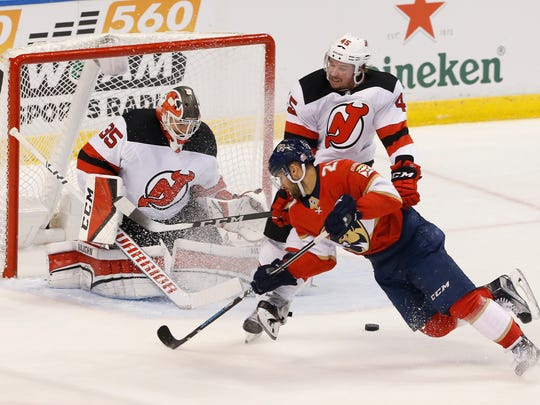 Florida Panthers center Vincent Trocheck (21) can't score as New Jersey Devils goaltender Cory Schneider (35) and Sami Vatanen (45) defend during the second period of an NHL hockey game, Thursday, March 1, 2018, in Sunrise, Fla.