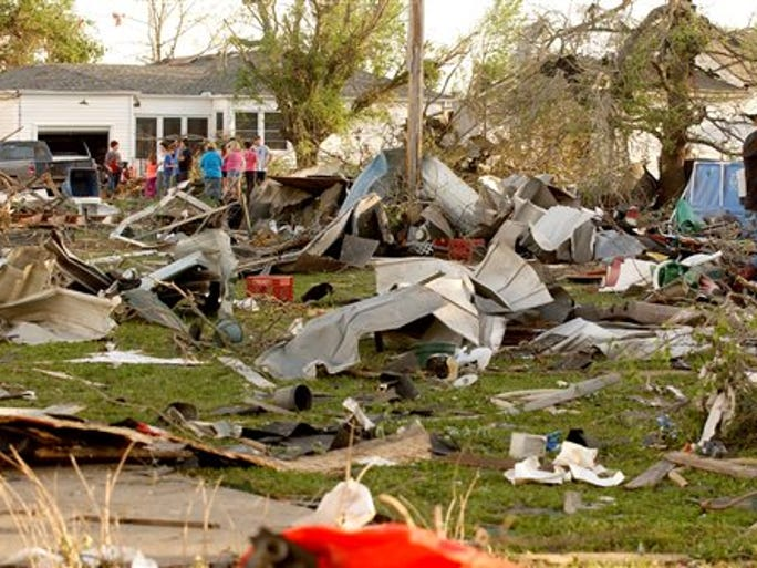 Quapaw, Okla.,  residents survey the damage in a residential neighborhood struck by a tornado on Sunday evening, April 27, 2014. A powerful storm system rumbled through the central and southern United States on Sunday, spawning a massive tornado that carved path of destruction through the northern Little Rock suburbs and another twister that hit in Oklahoma.