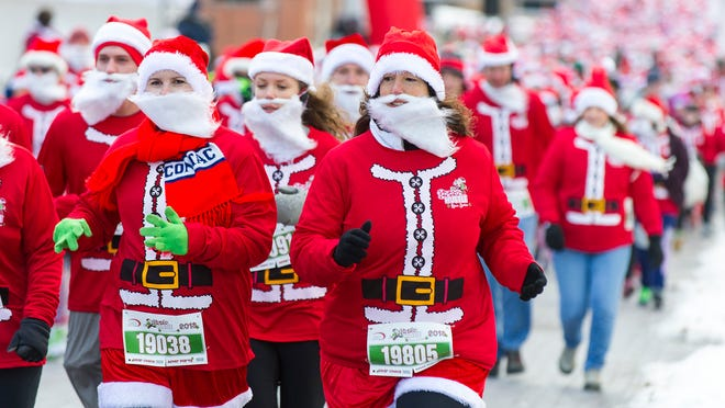 Ruth Lynch, left, and Jodi Verhoeven head out onto the course. Over a thousand Santa-clad runners participated in the 3rd Annual Santa Hustle 5k and half marathon race at White River State Park Sunday, Dec. 15, 2013.