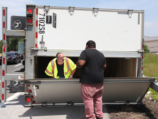 A Rye firefighter kneels from inside the trailer of a truck that overturned  and talks to the driver, June 4, 2014. The rollover occurred on Exit 21 off of I-95 in Rye. The exit allows motorists onto Interstate 287 westbound and Port Chester.