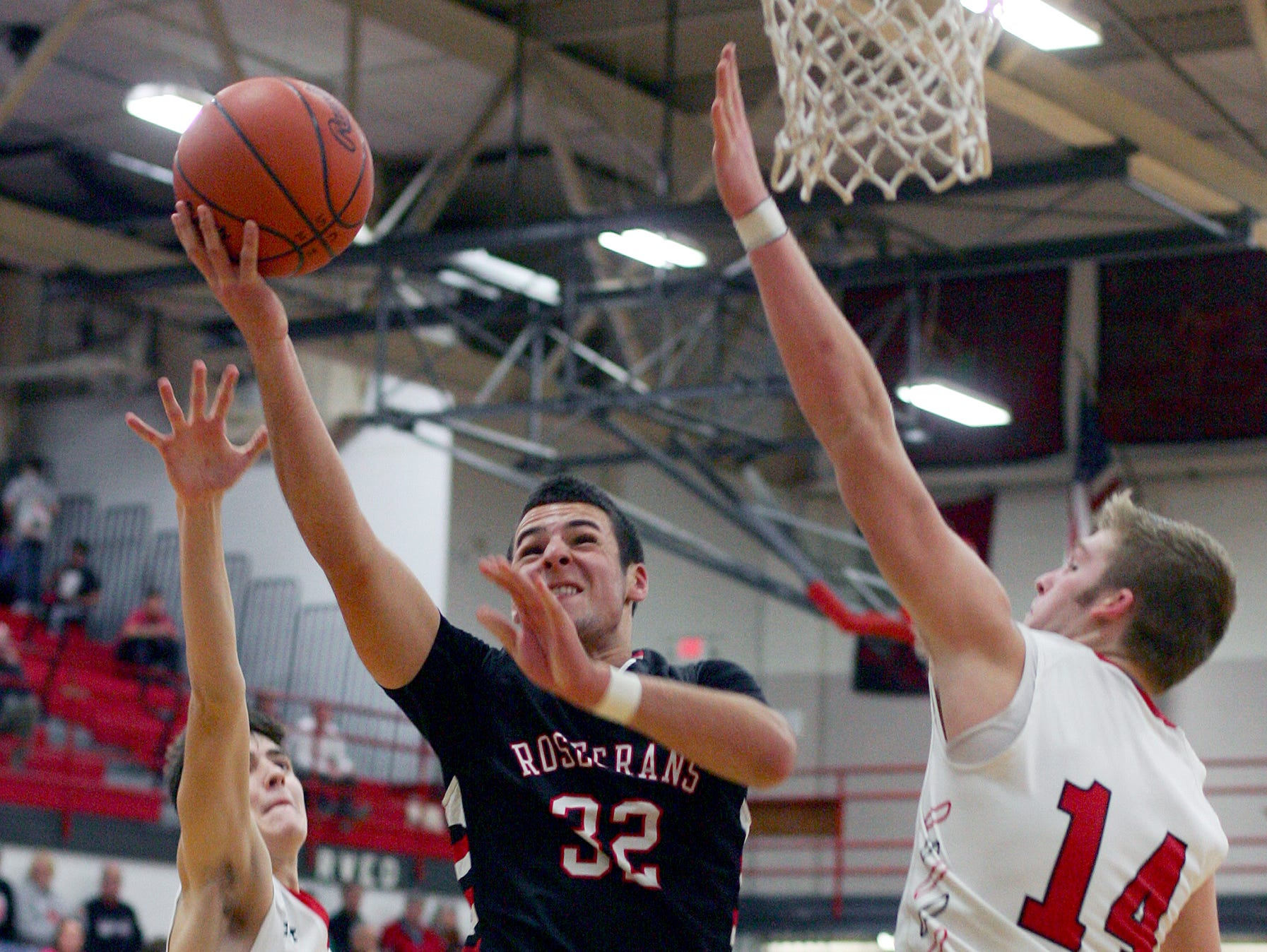 Bishop Rosecrans junior Aaron Gehlken drives to the basket under pressure from Coshocton junior Ashton Jarvis and junior Andrew Mason Friday during the Bishops' 69-68 victory in overtime.