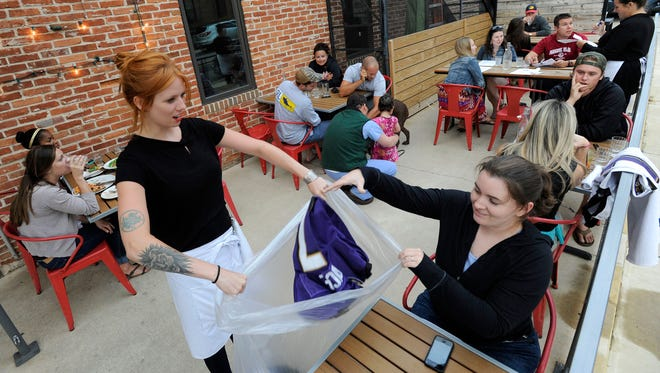 Bartender Abby Hopper, left, of Baltimore, collects a Ray Rice Baltimore Ravens football jersey from Erin McGonigle, right, of Arbutus, Md., at Hersh's Pizza and Drinks, a Baltimore restaurant that offered a free personal pizza in exchange for Rice jerseys.