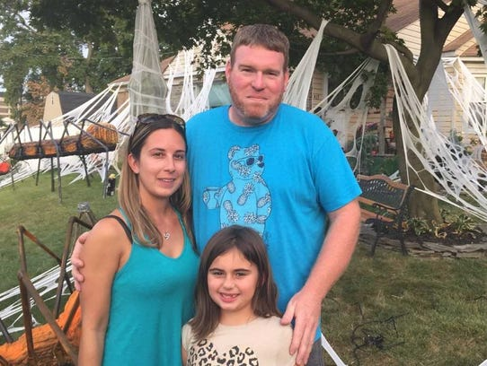 Tabitha and Josh Robinson stand with daughter Angelina,