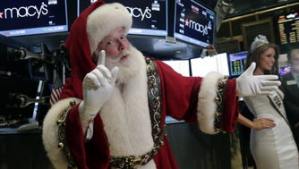 Santa Claus and Nia Sanchez, Miss USA 2014, who will be in the Macy's Thanksgiving Day Parade, visit the trading floor after participating in opening bell ceremonies of the New York Stock Exchange, Wednesday, Nov. 26, 2014. Stock indexes are holding near record levels as traders digest some mixed news on the U.S. economy. (AP Photo/Richard Drew) ORG XMIT: NYRD109