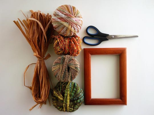 Use strips of yarn, ribbon and raffia to decorate a basic frame.