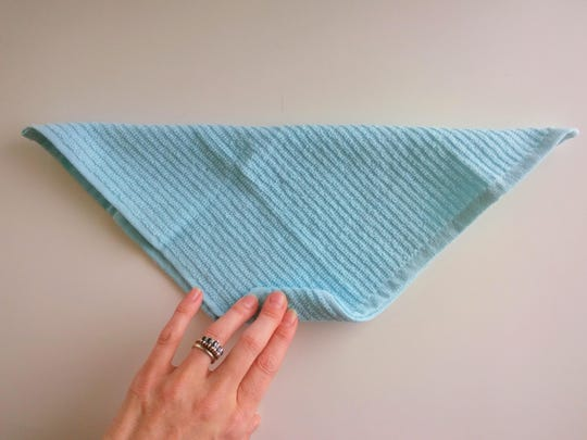 Fold washcloth in half crosswise, matching corners (to create a triangle). Starting at the point where you matched the two corners, fold the washcloth over itself.