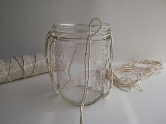 Tuck twine, folded it in half, under another length of twine tied at the neck of the jar. Space them evenly at the top so they are divided equally around the perimeter of the jar.