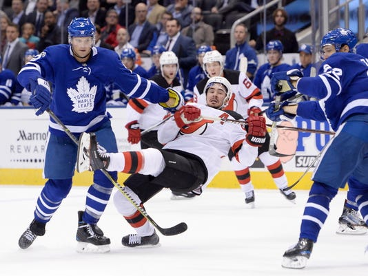 Toronto Maple Leafs defenseman Ron Hainsey (2) knocks down New Jersey Devils left wing Marcus Johansson (90) during the third period of an NHL hockey game Wednesday, Oct. 11, 2017, in Toronto. (Nathan Denette/The Canadian Press via AP)