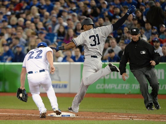 New York Yankees' Aaron Hicks (31) beats the throw to first base as Toronto Blue Jays relief pitcher Seung-hwan Oh is late to the bag during the eighth inning of a baseball game in Toronto on Thursday, March 29, 2018. (Nathan Denette/The Canadian Press via AP)