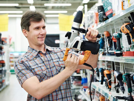 A shopper tries out a power drill.