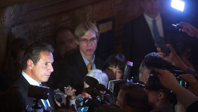 New York Gov. Andrew Cuomo, left, talks to media members outside his office at the state Capitol on Wednesday, March 30, 2016, in Albany, N.Y. Cuomo says legislative leaders have agreed to a $150 billion state budget plan that includes a minimum wage hike and $1 billion in middleclass income tax relief. (AP Photo/Mike Groll)