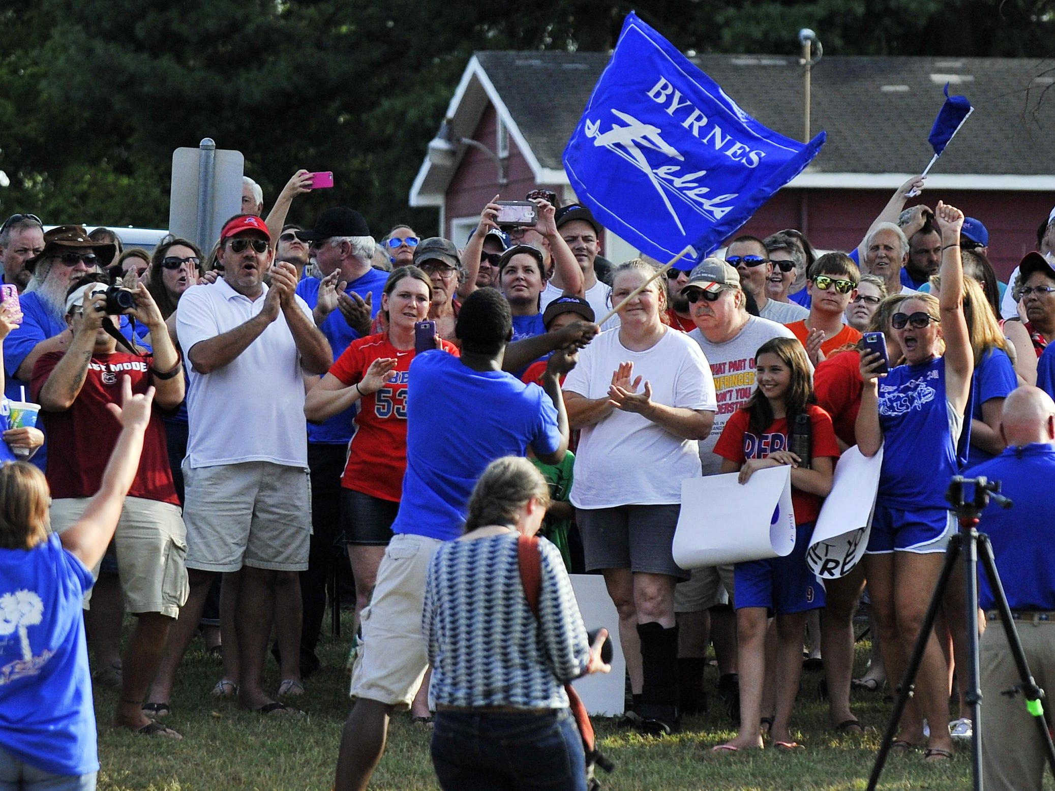 """A large group of supporters of the Byrnes High School """"Rebels"""" nickname gathered across from the school to rally on Monday, July 20, 2015."""