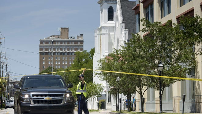 A police officer holds up a tape in front of the Emanuel AME Church June 18, 2015 in Charleston, South Carolina, after a mass shooting at the church on the evening of June 17, 2015. US police on Thursday arrested a 21-year-old white gunman suspected of killing nine people at a prayer meeting in one of the nation's oldest black churches in Charleston, an attack being probed as a hate crime. The shooting at the Emanuel African Methodist Episcopal Church in the southeastern US city was one of the worst attacks on a place of worship in the country in recent years, and comes at a time of lingering racial tensions. AFP PHOTO/BRENDAN SMIALOWSKIBRENDAN SMIALOWSKI/AFP/Getty Images