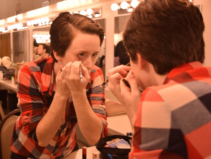 Madelyn James puts on eye makeup as she prepares for