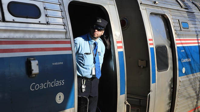 Amtrak conductor Jason Dunigan of looks out the coach door as the Downeaster pulls into the Dover Transportation Center.