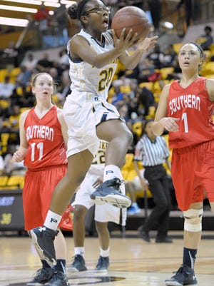 Pcomoke's Tymera DeShields, center, glides between Southern-Garrett's Courtney Roth, left, and Lauren Francillon, right, in the second half of a Class 1A state girls basketball semifinal, in Towson, Friday, March 11, 2016. (Photo by Steve Ruark)