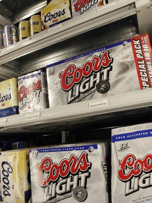 Twelve packs and 18 packs of Coors Light and Coors beer share space in a cooler in a liquor store in southeast Denver.