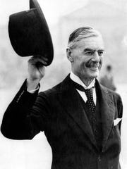 Neville Chamberlain waves his hat on his 71st birthday