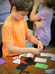 Gavin Runnerstrom creates a library card holder at the open house marking Farnsworth Public Library's 115th anniversary on June 28.