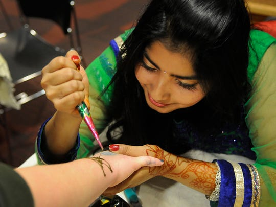 A student gives a Henna tattoo at the Bangladesh booth at the Passport to the World event at St. Cloud State on Sunday.
