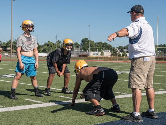 Coaches work with kids during a football camp at Battle