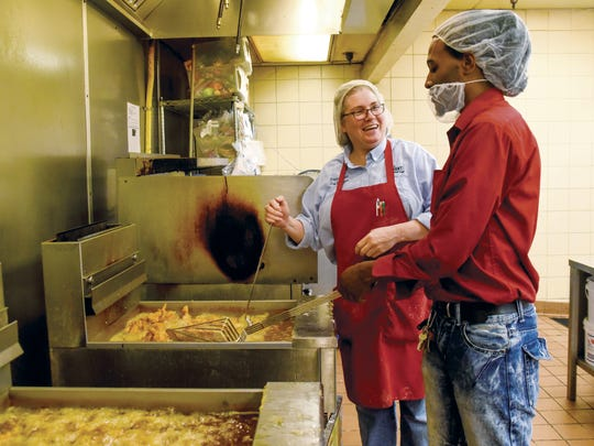 Deli manager Bobbie Reese and store manager Ty Dankins take chicken from the fryer at Food Giant in Columbus on a recent Wednesday afternoon. The store on Alabama Street in east Columbus sells more than six tons of fried chicken each week.