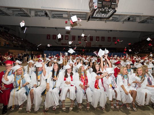 Graduates throw their caps into the air during the
