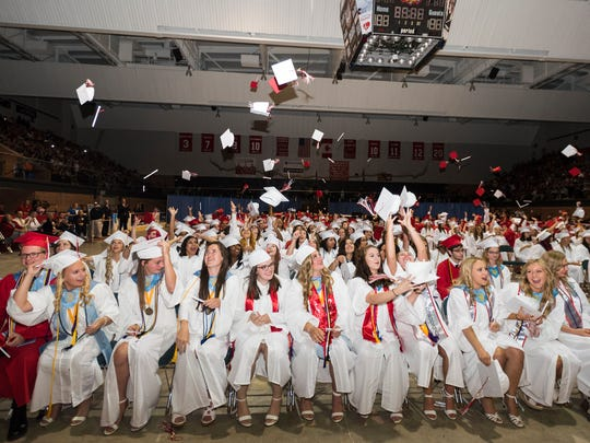 Graduates throw their caps into the air during the Port Huron High School commencement ceremony Wednesday, June 6, 2018, at McMorran Arena.