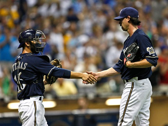 Milwaukee Brewers' John Axford shakes hands with George