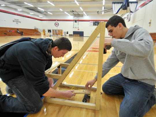 Denmark High School's Collin Klaubauf, 15, left, and Isaac Blakeslee, 14, set up at a station to run their car during Saturday's Wisconsin Science Olympiad at the University of Wisconsin Marathon County in Wausau.
