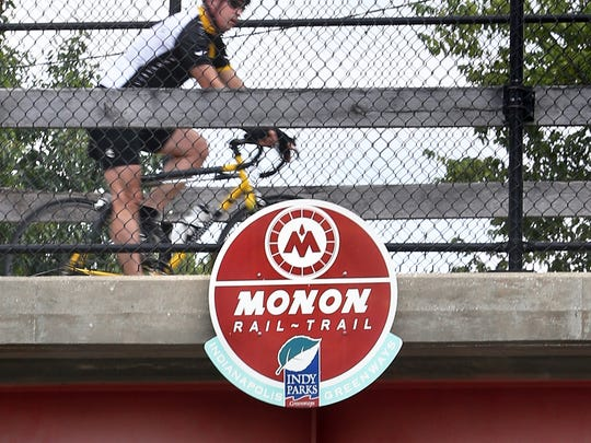 A bicyclist uses the Monon Trail where it crosses over the 1100 block of Fairfield Avenue, just south of the Indiana State Fairgrounds, on Aug. 27, 2014. The Indianapolis parks board has voted to temporarily extend the hours of the Monon Trail and other greenways to 5 a.m. to midnight.