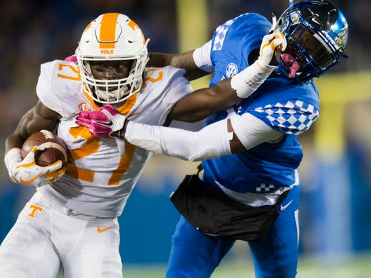 Tennessee running back Carlin Fils-aime (27) runs the ball as he attempts to keep Kentucky safety Mike Edwards (7) away during the Tennessee vs. Kentucky game at Kroger Field in Lexington, Kentucky Saturday, Oct. 28, 2017. Kentucky defeated Tennessee 29-26.
