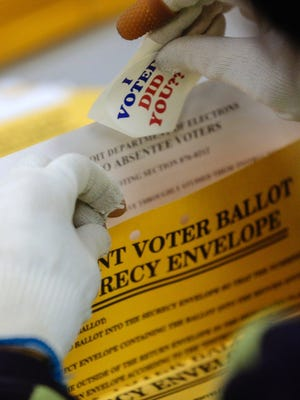 A worker adds stickers for absentee voters while preparing ballots to send out on Wednesday October 29, 2014 at the City of Detroit Department of Elections in Detroit before being able to count them on election day.