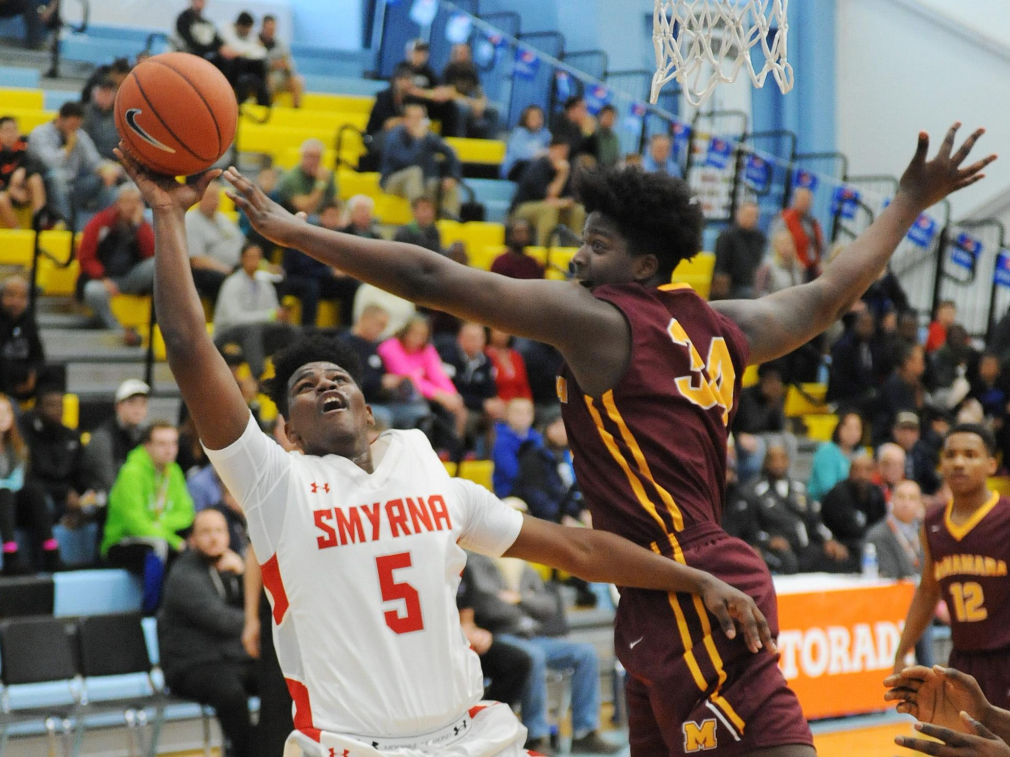 Smyrna's #5 Jaymeir Garnett gets 2 points as Bishop McNamara'a Makhel Mitchell attempts block as The Annual Slam Dunk to the Beach Basketball Tournament started at Cape Henlopen High School in Lewes on Tuesday December 27th with Smyrna HS (white) hosting Bishop McNamara HS from Forestville, Md.