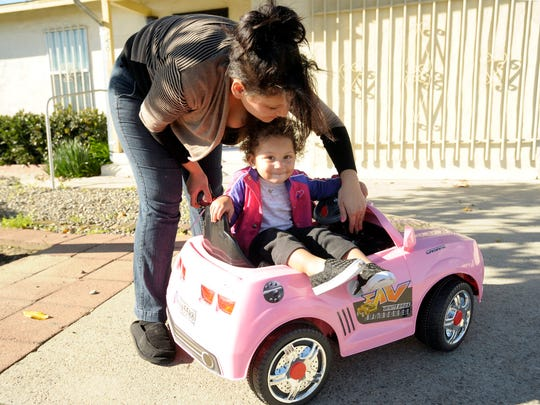 Kimberly Brindle and her daughter, Heaven, 1, play with Heaven's new remote-controlled Camaro near their home in Visalia.