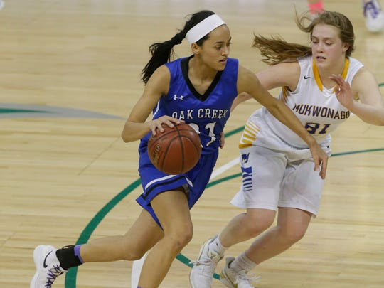 Oak Creek's Kassandra Bartek drives to the basket against Mukwonago's Kat Lopez during the first half of a 2018 WIAA state semifinal game Friday, March 9, 2018, at the Resch Center in Green Bay.