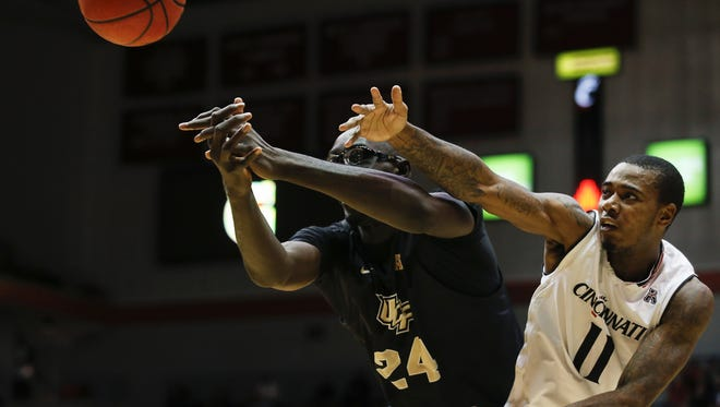 Central Florida's 7-foot-6 center Tacko Fall, here battling Cincinnati's Gary Clark for a loose ball in a game last season, will not play Tuesday when UCF visits the Bearcats. Fall is out for the season with a shoulder injury.