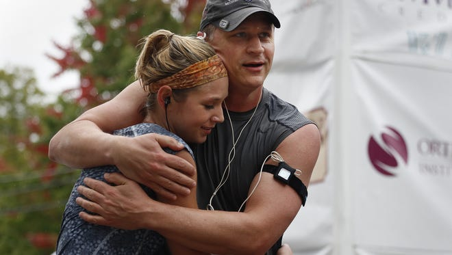 Tim Hopfensperger hugs his daughter, Alyssa, after crossing the finish line of last year's Community First Fox Cities Marathon.