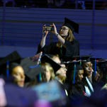 A West Florida graduate snaps some photos Saturday during the UWF Spring Commencement at the Pensacola Bay Center.