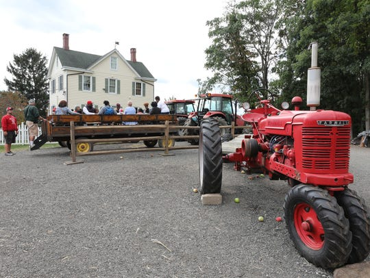 People prepare to take a tractor ride through the orchards