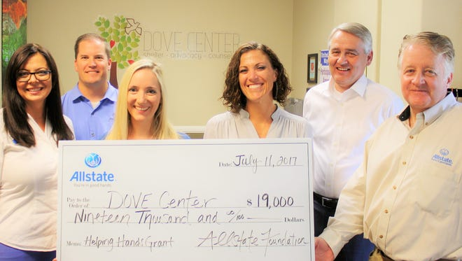 Allstate agency owners pose with a $19.000 check representing a grant the company's charity raised for the DOVE Center, a nonprofit that provides support for survivors of domestic abuse.