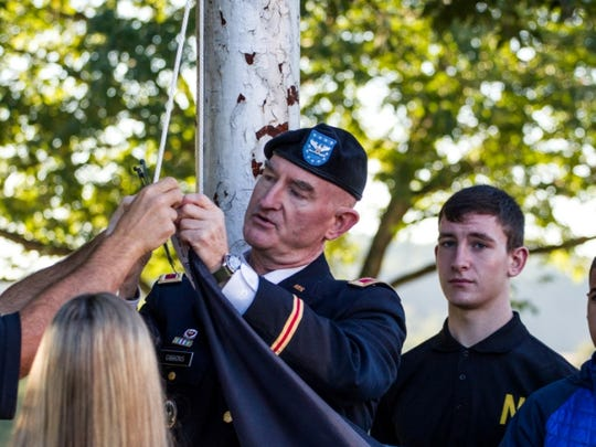 Colonel Jim Gibbons, his son and junior Brinton Gibbons and other Patriotic Youth Council members raise the POW/MIA flag at North Hunterdon High School.