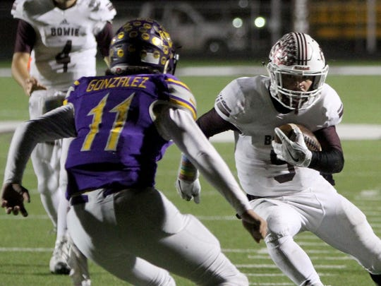 Bowie's Brandon Hutto tries to evade Merkel's Tatian Gonzalez in the 3A Divison I bi-district playoff Thursday, Nov. 10, 2016, at Fair Park Stadium in Seymour.
