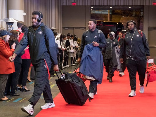 Members of the Georgia football team arrive at an Atlanta hotel Friday, Jan. 5, 2018. Georgia plays Alabama in the College Football Playoff title game Monday in Atlanta. (Alyssa Pointer/Atlanta Journal-Constitution via AP)