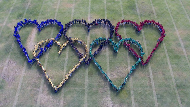 Creating hearts to form like the Olympic rings, Loving students took an aerial photo Thursday morning to commemorate the beginning of the district's own Olympics.